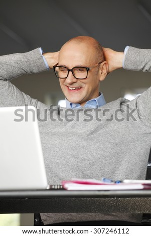 Close-up portrait of senior businessman standing at office in front of laptop and thinking while working online.