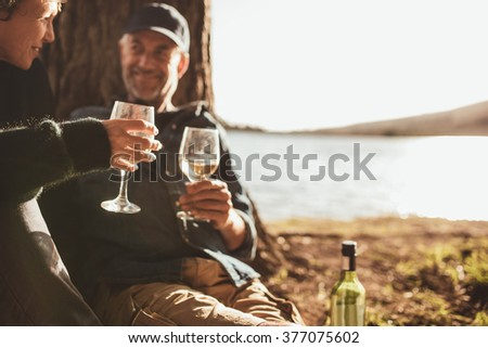 Close up portrait of senior couple drinking wine while camping near a lake. Focus on hands holding glass of wine. - stock photo