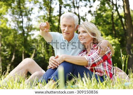 Close-up portrait of senior couple relaxing in the nature. Mature woman sitting next to old man while he shows something with his finger.