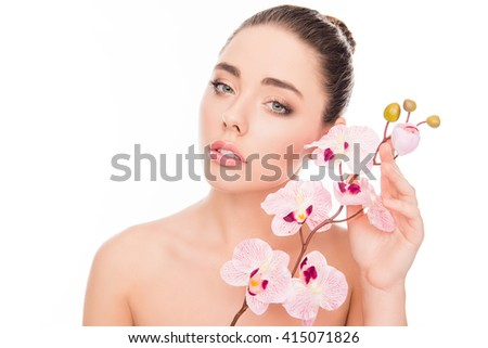 Close up portrait of sensitive woman holding orchid near face - stock photo
