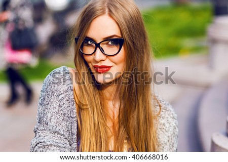 Close up portrait of sensual blonde woman with full red lips, stylish glasses for sight. Young lady walking   in old European city.   - stock photo