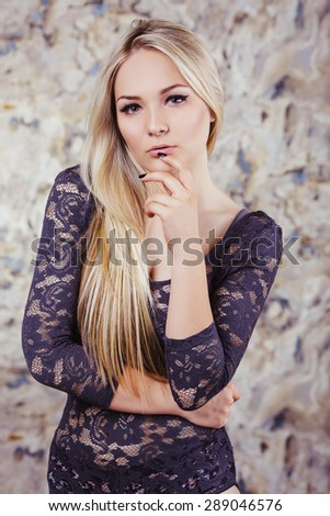 Close up portrait of sensual young blonde woman. In fashionable sensual dark lingerie. Posing in studio. - stock photo