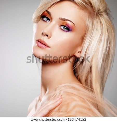 Close-up portrait of sensual young woman in the beige fabric over gray background. - stock photo