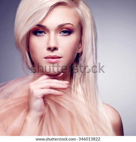 Close-up portrait of sensual young woman touching her face in the beige fabric over gray background. - stock photo