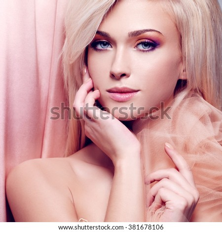 Close-up portrait of sensual young woman touching her face in the beige silk. - stock photo