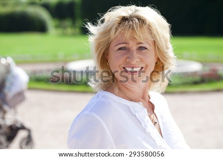 Close up portrait of serene mature woman in the summer park  - stock photo