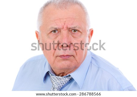 Close-up portrait of serious and strict senior old businessman, dressed in blue shirt and tie, isolated on white background. Human emotions and facial expressions