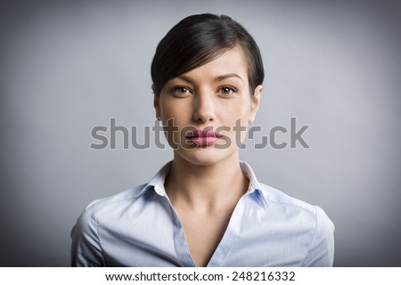 Close up portrait of serious, confident businesswoman looking straight, isolated on grey background. - stock photo