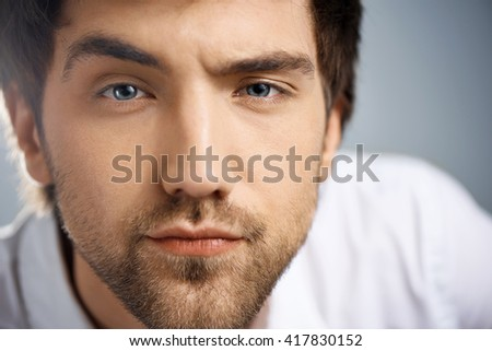 Close up portrait of serious elegant handsome young businessman in white shirt looking at camera raising one eyebrow. Studio, isolated on grey background. - stock photo