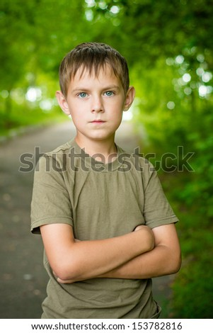 Close up portrait of serious little boy with folded hands outdoo - stock photo