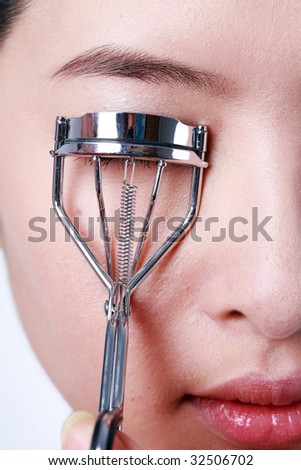 Close-up portrait of sexy asian young woman holding eye lash curler - stock photo