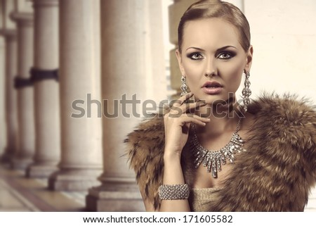 close-up portrait of sexy blonde woman with aristocratic style posing with charming expression and elegant hair-style. Wearing fur shawl and very precious jewellery. Glamour look  - stock photo
