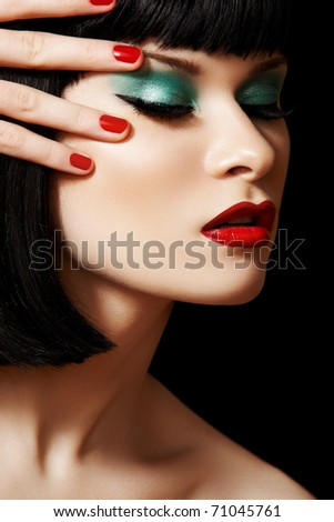 Close-up portrait of sexy european young woman model with retro glamour make-up and red bright manicure. Dark bob hairstyle, christmas makeup, green eyeshadows, bloody red lips with gloss - stock photo
