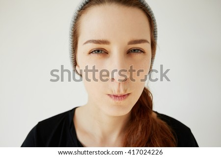 Close up portrait of skeptical young woman looking suspicious, with disgusted expression on her face, mixed with disapproval, isolated against white background. Negative human emotions, and feelings - stock photo
