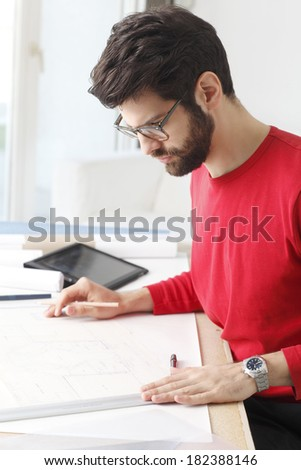 Close-up portrait of small architect studio owner sitting at desk .