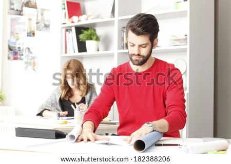 Close-up portrait of small architect studio owner sitting at desk . - stock photo