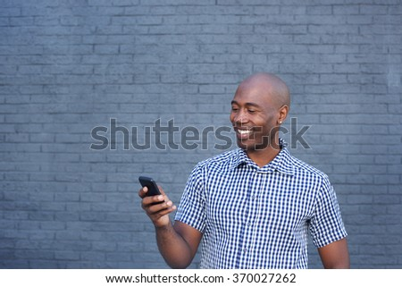 Close up portrait of smiling african man looking at mobile phone - stock photo