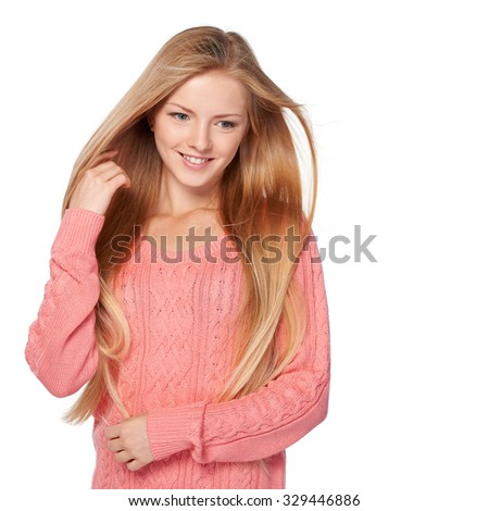 Close up portrait of smiling beautiful blond female in pink sweater with hair lightly fluttering in the wind, over white background - stock photo