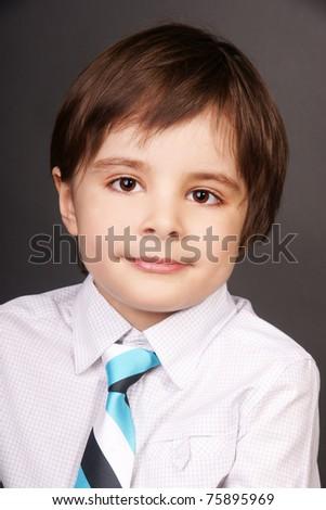 Close-up portrait of smiling beautiful stylish little boy, studio shot - stock photo