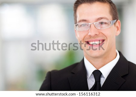 close up portrait of smiling businessman in office