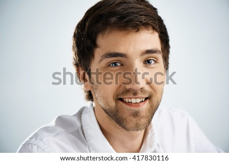 Close up portrait of smiling elegant confident handsome young businessman in white shirt looking at camera. Studio, isolated on grey background. - stock photo