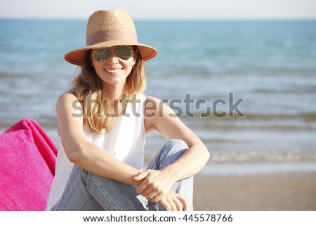 Close-up portrait of smiling female by the sea. Happy woman sitting at the seaside and looking at the camera.