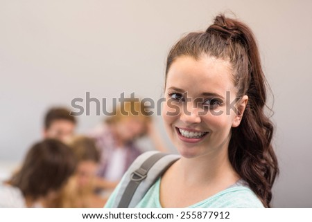 Close up portrait of smiling female student in classroom - stock photo