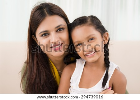 Close-up portrait of smiling Indian mother and daughter - stock photo