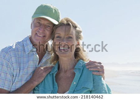 Close up portrait of smiling senior couple on sunny beach