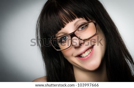 Close-up portrait of smiling woman with glasses on gray background