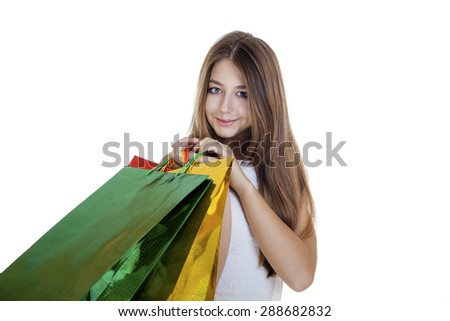 Close up portrait of smiling young blonde girl with colorful shopping bags in white dress posing on a white background - stock photo