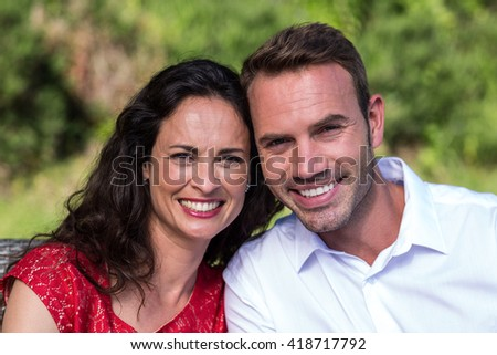 Close-up portrait of smiling young couple sitting in lawn - stock photo