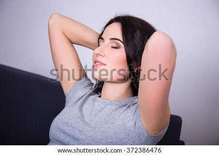 close up portrait of smiling young woman lying on couch - stock photo