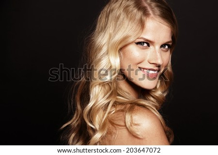 close-up portrait of smiling young woman with curly blond hair - stock photo