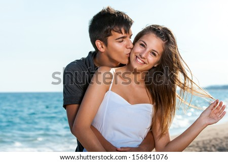 Close up portrait of teen couple embracing on beach. - stock photo