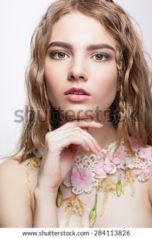 Close-up portrait of teen girl with flower necklace and hand near face - stock photo