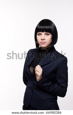 Close up  portrait of the beautiful young woman in a business suit on a light background