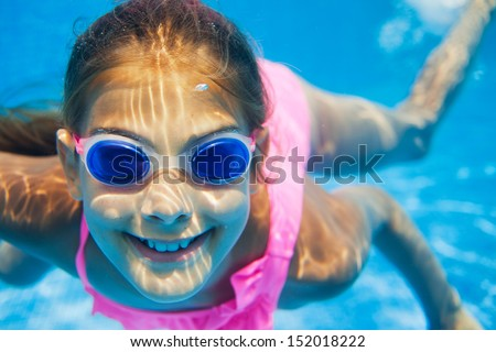 Close-up portrait of the cute girl swimming underwater and smiling - stock photo