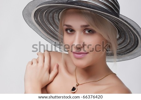 close up Portrait of the nice young woman in a hat on a light background - stock photo