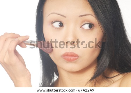 Close-up portrait of the young woman with makeup brush - stock photo