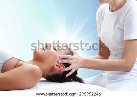 Close up portrait of therapist doing healing treatment on young woman.Therapist touching head with light glow in background. - stock photo