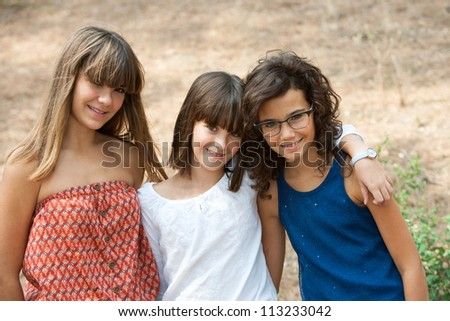Close up portrait of three cute teenage girlfriends outdoors. - stock photo