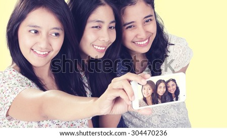 Close up portrait of three happy Asian girls take picture of themselves with cellphone camera, in soft color tone - stock photo