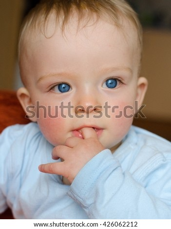 Close-up portrait of toddler sucking his finger. Beautiful boy has blue expressive eyes. Child concept. - stock photo