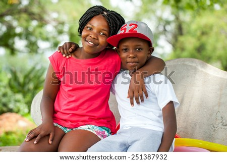 Close up portrait of two African kids sitting together on bench in park. - stock photo
