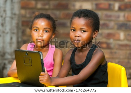 Close up portrait of two african kids with digital tablet outdoors. - stock photo