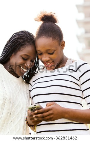 Close up portrait of two African teen girlfriends texting on smart phone outdoors. - stock photo