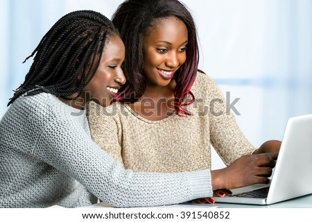 Close up portrait of two attractive african teen girls sitting together at table. Girl with braided hair pointing at computer screen. - stock photo