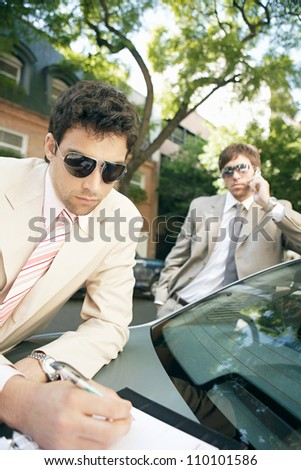 Close up portrait of two attractive businessmen meeting in a tree lined street, making calls and taking notes. - stock photo