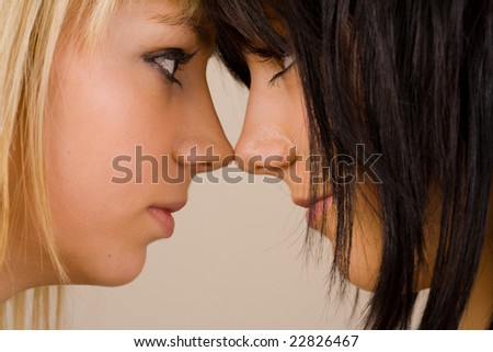 Close up portrait of two beautiful girls with opposite hair color (blonde and brunette) - stock photo